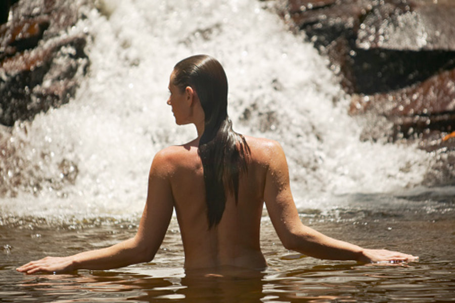 nude woman under a waterfall