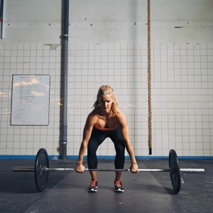 Strong young woman lifting heavy weights at gym. Fitness female doing crossfit workout.