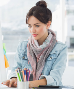 Concentrated casual young woman using computer in a bright office