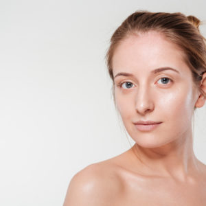 Beauty portrait of a young woman with clean skin looking at camera isolated on a white background