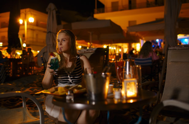 Young woman enjoying a drink in a pub or restaurant sitting at a table alone outdoors illuminated by electric lamps sipping a drink