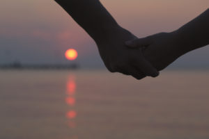 Close up of the hands of a romantic couple holding hands at sunset silhouetted against the colourful night sky with the orb of the sun visible below