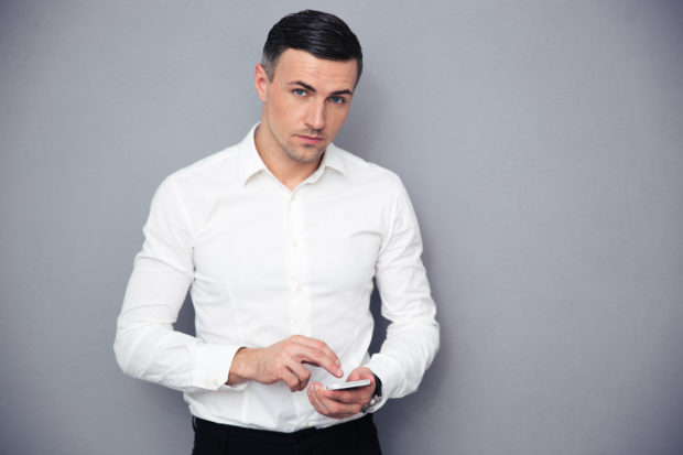 Serious businessman using smartphone and looking at camera over gray background
