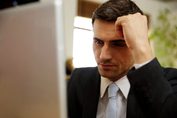 Pensive businessman using laptop at office