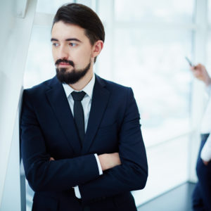 Image of calm businessman in office with his colleague on background