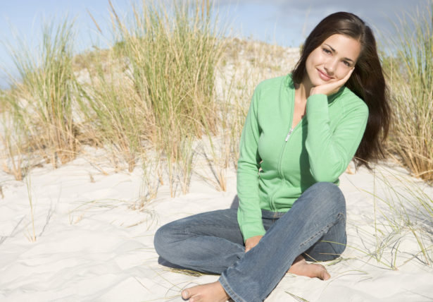 Young woman relaxing amongst dunes