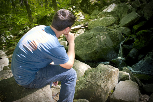 A young man in deep thought while sitting on some rocks near a beautiful waterfall.