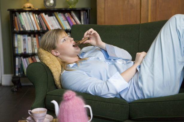 A young woman lying on her couch eating chocolate