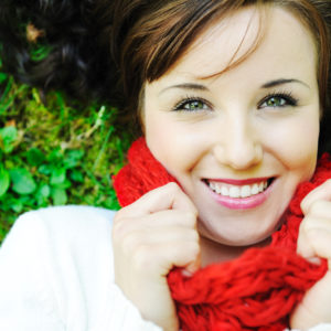 Closeup portrait of a beautiful woman lying on ground  and smiling