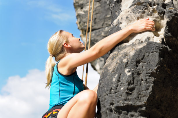 Rock climbing blond woman on rope sunny