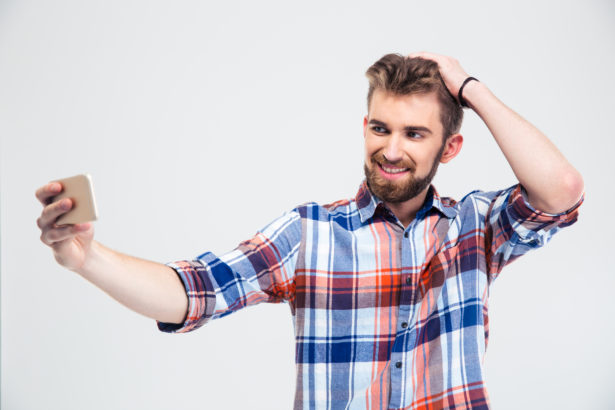 Portrait of a cheerful casual man making selfie photo on smartphone isolated on a white background
