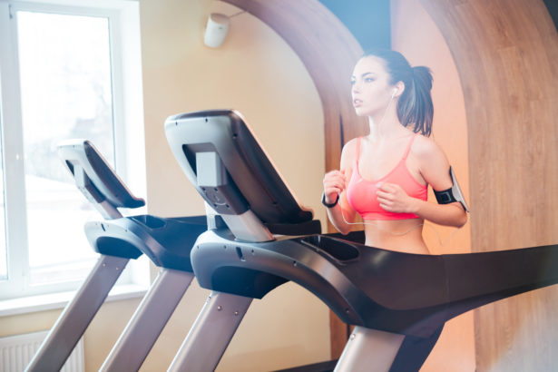 Pretty focused young woman athlete running on treadmill in gym