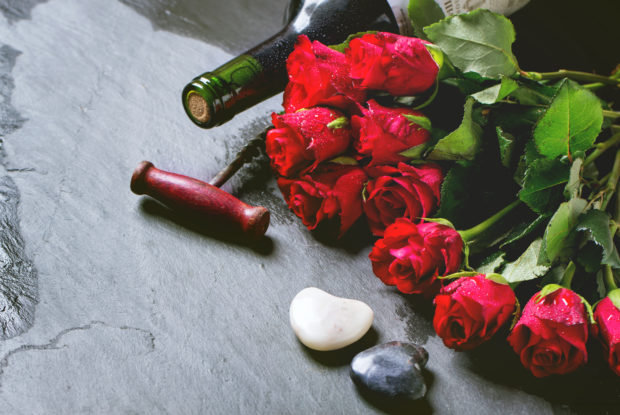 St Valentine greeting card with red roses, heart and wine at black stone background. See series