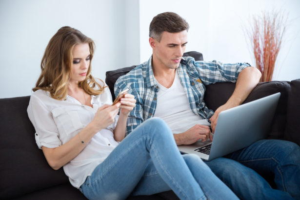 Beautiful couple using laptop and smartphone separately