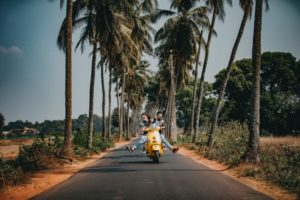 Couple riding bike by coconut trees